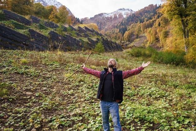 雄大な山の風景の前に立っているハイカー