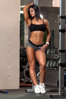 若いフィットネス女性がジムでプルアップ完璧な筋肉ボディのスポーツウェアのブルネットフィットネス女性
