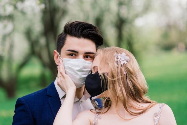 結婚式の日の検疫中に公園で医療マスクで歩く若い夫婦。コロナウイルス、病気、保護、病気、病気のインフルエンザのヨーロッパのお祝いはキャンセルされました。