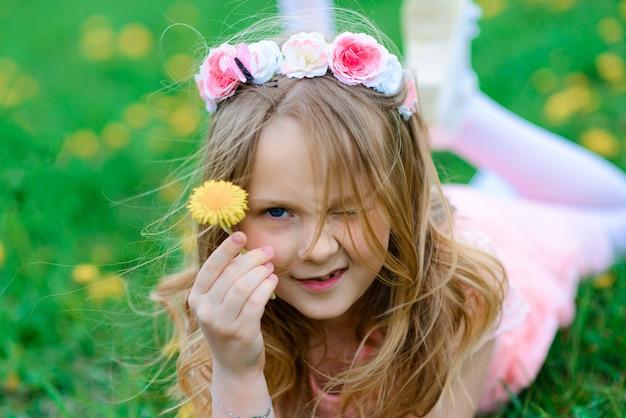 Милая девушка ребенка усмехаясь и играя в цветках сада, зацветая деревьях, вишне, яблоках.