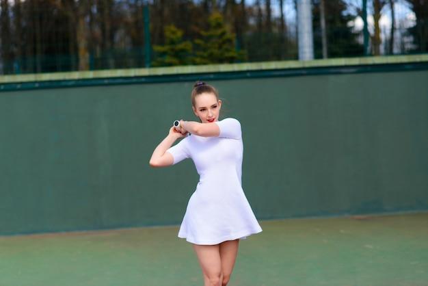 Игрок тенниса сексуальной девушки держа ракетку тенниса на суде.