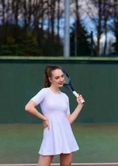 Сексуальная девушка теннисистка в белом платье и на каблуках держит теннисную ракетку на корте.
