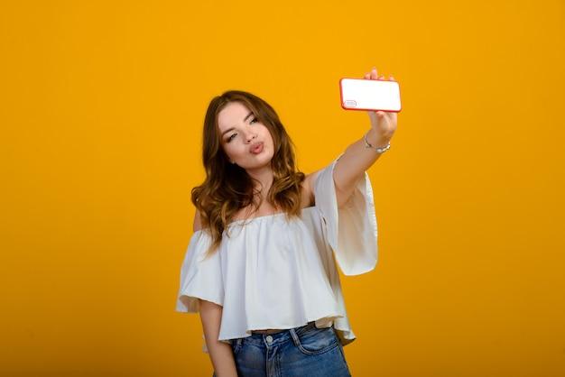 デジタルデバイスで興奮した女性。感情的なスマートフォンを保持しているショックを受けた少女のショット