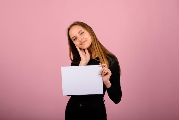 電話と空白の看板と美しい若い女性の肖像画。ピンク色の空間でポーズをとって白人金髪モデル。