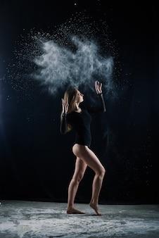暗闇の中で小麦粉をまとった黒いボディースーツの長い髪の少女。