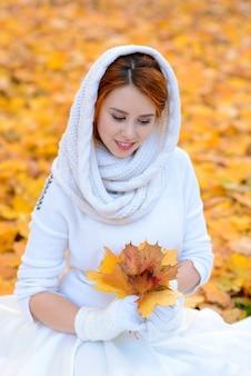 Милая девушка в длинном белом платье свадьбы представляя в сельском пути среди осенних деревьев в лесе в атмосфере золотого часа.