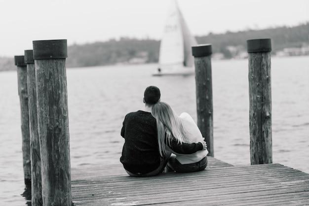 Сало, италия. романтическая молодая пара, сидя на скамье подсудимых