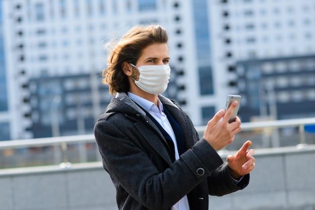 外の医療マスクの若い男、お金、危機、貧困、困難。検疫、コロナウイルス、隔離。