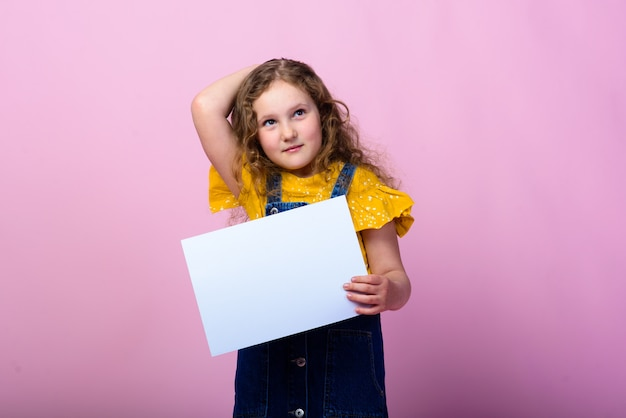 Милая маленькая девочка с белым пустым листом бумаги розового фона