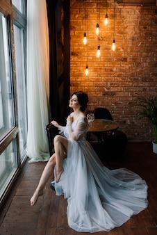 花嫁はヨーロッパ風のブルネットです。シングルポートレート。結婚式のメイクや髪型。花嫁の朝。ホテルの私室。