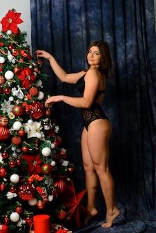 暖炉の近くポーズレースの黒いランジェリーでホットな美しい女性。クリスマスのインテリア。