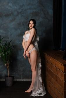 Красивая невеста в белом белье сидит в своей спальне