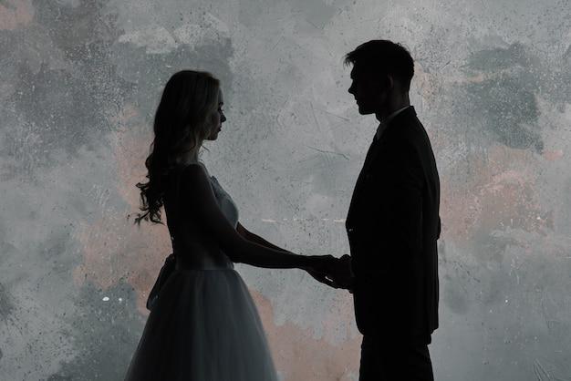 飾られたクラシックルームのインテリアでかわいい結婚式のカップル。彼らはお互いにキスして抱擁します。