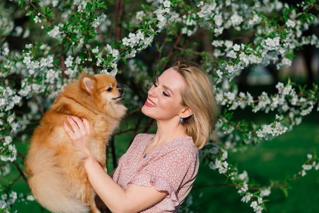 魅力的な若い女性は犬のスピッツを保持し、カメラに笑顔、公園を散歩しています。