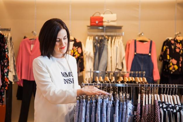 服を選ぶ洋服店の若い女性。