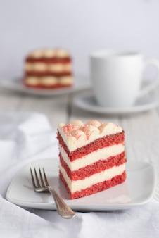 赤いベルベットケーキのスライスとコーヒーのカップ。白色の背景。