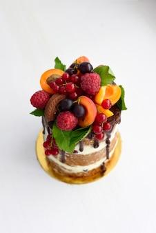 白い背景の上の果実で飾られた小さな裸の丸いケーキ