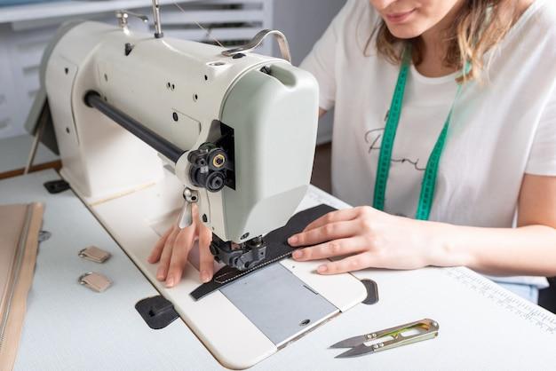 Девочка шьет на швейной машине каракули ткани и кожи, делая изделие