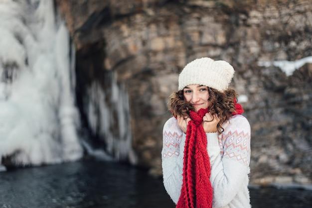 滝の近くの冬の赤いスカーフの女の子