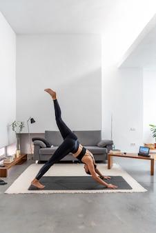 Женщина делает одну ногу вниз лицом собаки, используя онлайн-программу обучения йоге в планшете дома