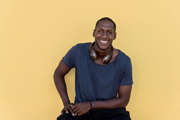 Портрет африканского человека с наушниками смеясь над красочной стеной