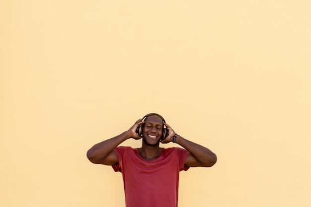 Портрет уверенной молодой взрослой слушающей музыки на красочной стене