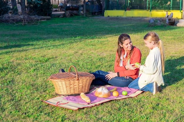 母は公園で彼女の娘にリンゴを与えます