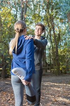 健康なカップルが公園で実行した後、ストレッチ体操をしています