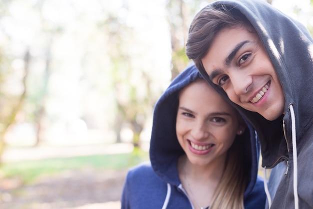 Крупным планом улыбающихся пара с толстовки на открытом воздухе