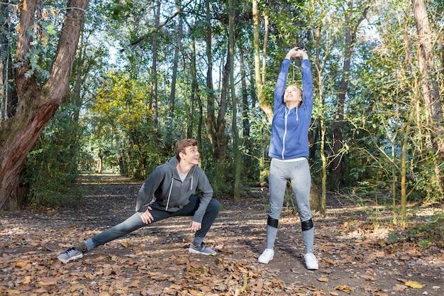 Друзья в спортивной одежде делает растяжку в солнечный день
