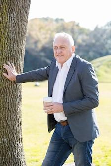 哀愁を秘めたビジネスマンは、屋外でコーヒーを飲みます