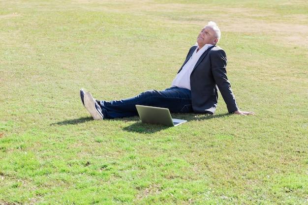 芝生の上で休んでシニアエグゼクティブ