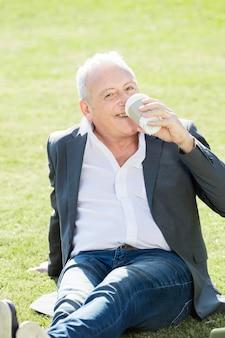 草の上に座って朗らかワーカー飲料コーヒー