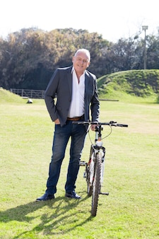 公園で彼の自転車とポーズ笑顔ビジネスマン