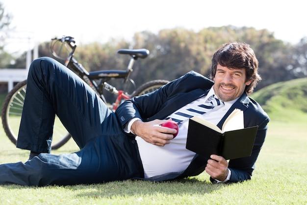 リンゴと屋外で本を保持するビジネスマン