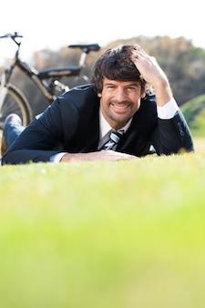 芝生の上で休んで笑顔ビジネスマン