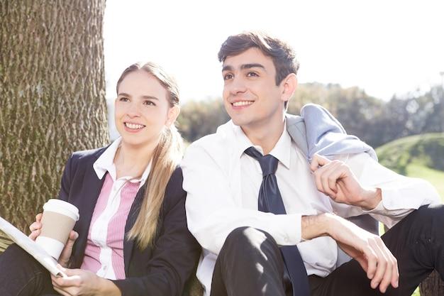 愛らしいカップルが屋外に座っ