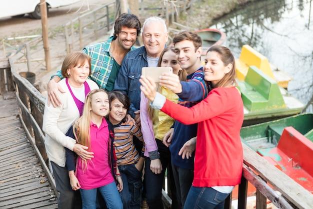 Веселая семья взятие селфи на открытом воздухе