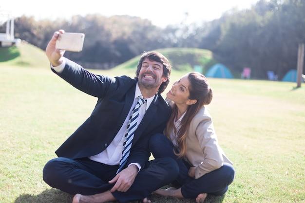 草の上に座って写真を撮る笑顔同僚