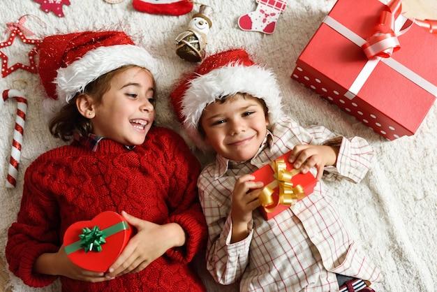 Девочка и мальчик носить шляпу санта