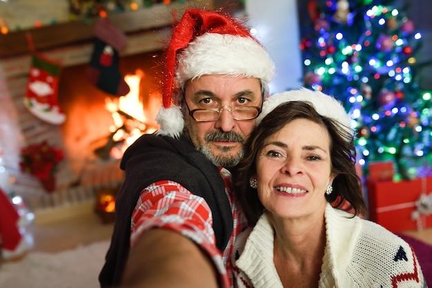 サンタの帽子を身に着けている祖父母