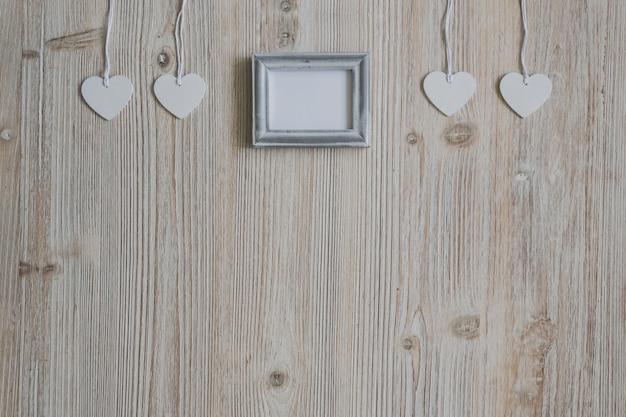 Белые сердца висит на веревке и пустой фото рамка в середине