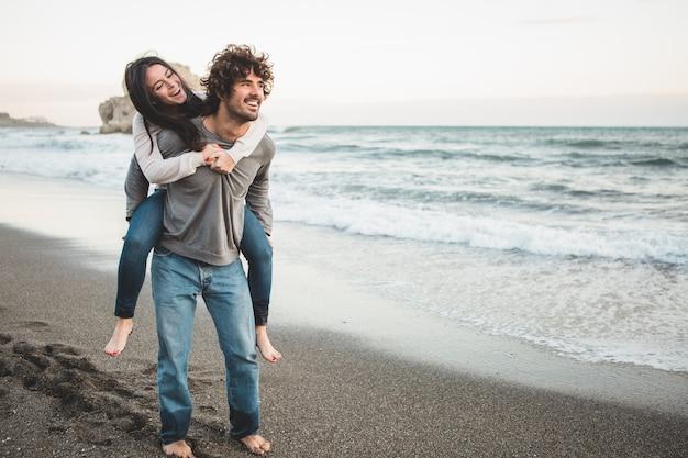 ビーチで男の背中に登る若い女の子