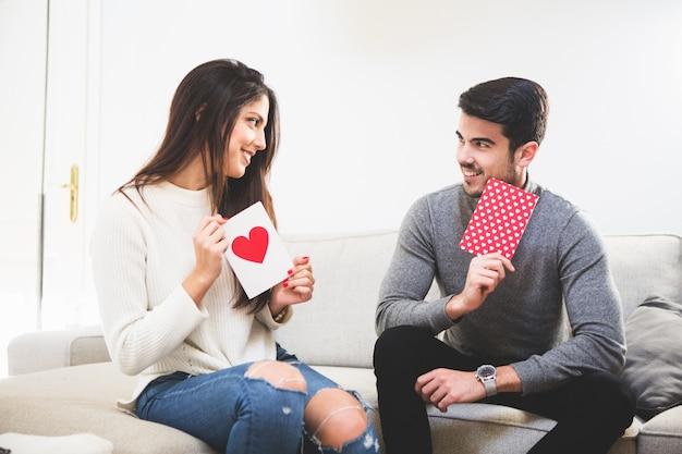 Улыбаясь пара глядя на открытки с сердцем