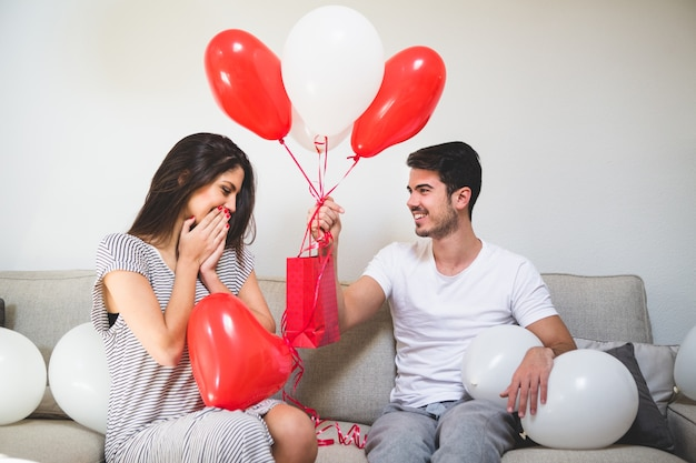 Человек протягивая свою подругу воздушные шары и красный мешок