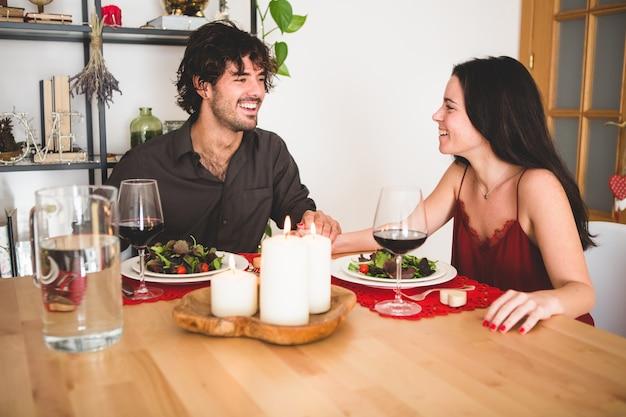 カップル笑顔食べるようにテーブルに座っ