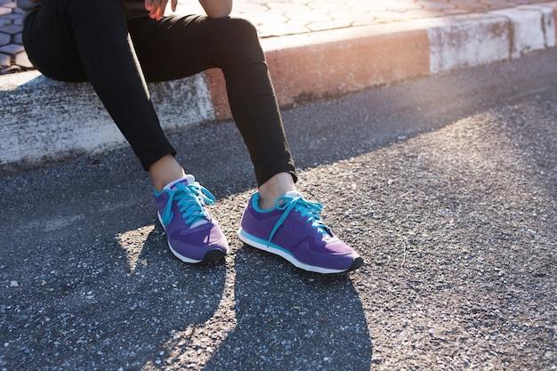 紫色のスニーカーでスポーティーな女性のクローズアップ