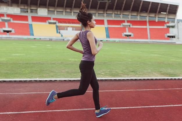 Активная девушка работает на стадионе
