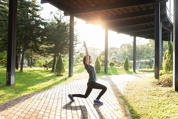 Гибкая женщина растяжения на открытом воздухе в солнечный день