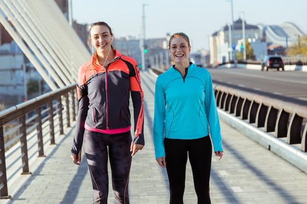 Счастливые молодые женщины в спортивной позы
